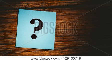 question mark against blue paper on wooden floor