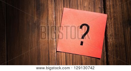 question mark against orange paper on wooden floor