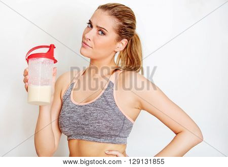 Young sporty woman with protein shake bottle