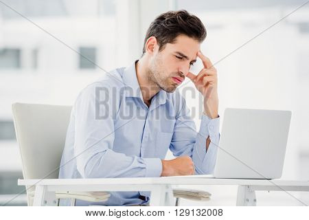 Tensed businessman sitting at table with laptop in office