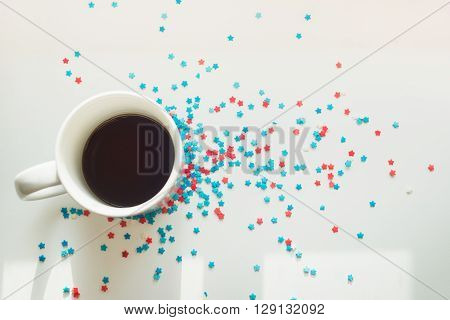sprinkles stars around a cup of coffee