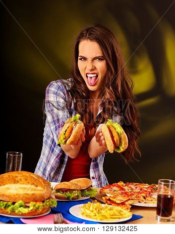 Girl refuses to eat fast food big hamburger and pizza . She demonstrates  aversion to fast food.