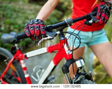 Bikes bicycling girl. Girl rides bicycle. Girl cycling fording throught water . Cycling middle section. Shorts and legs.