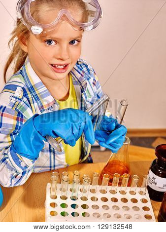 Child in blue rubber glove holding flask in chemistry class. Early learning chemistry children.