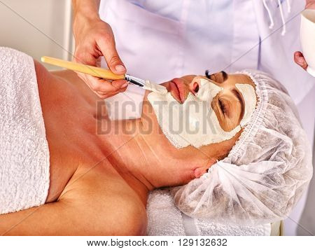 Woman middle-aged take facial and neck clay mask in spa salon. Anti-aging facial mask.