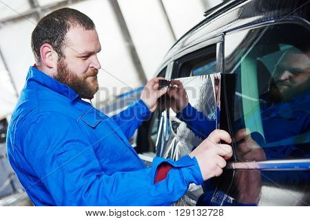 car tinting. Automobile mechanic technician applying foil