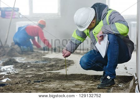 foreman builder inspecting concrete construction work in apartment