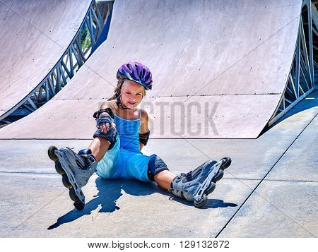 Girl in roller skates sitting on ride in skatepark. girl in fall protection in skatepark.