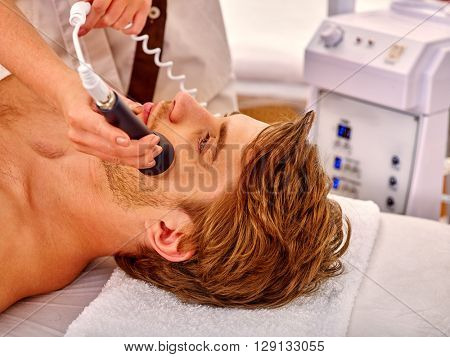 Young man luxuriating on electroporation  facial massage therapy at beauty salon. Man takes care of his face through facing massage.