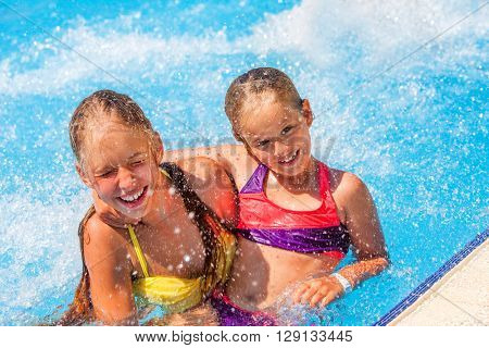 Two children in water at aquapark . Children hugging. Summer holiday.  Outdoor.