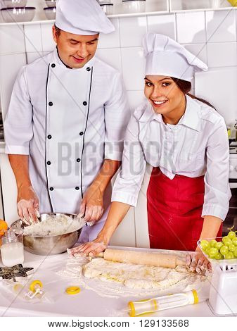 Happy woman and man in chef hat cooking dough  on professional kitchen. Small businesses.
