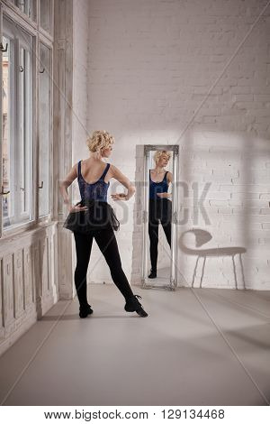 Ballet dancer training front of mirror in ballet studio.