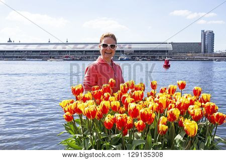 Young dutch woman with orange tulips behind central station in Amsterdam the Netherlands