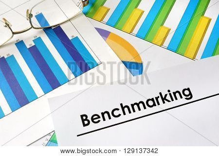 Paper with words Benchmarking, charts and glasses.