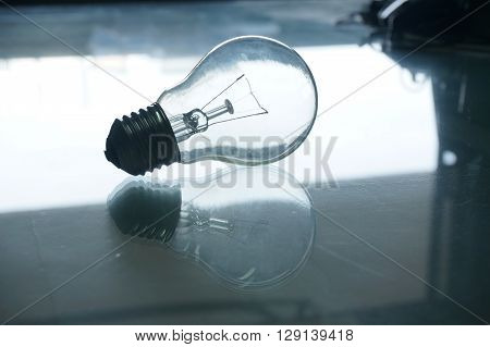 light bulb with reflections on glass table