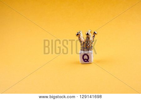 Crown on letter cube on a yellow background
