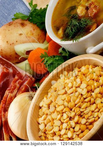 Arrangement of Yellow Pea and Ingredients of Pea Soup with Potato Carrot Leek Onion Parsley and Smoked Ham closeup