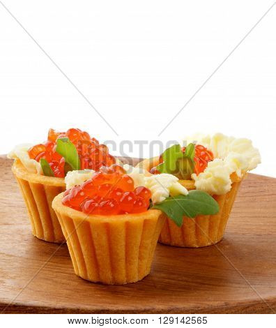 Perfect Red Caviar in Tartlets with Greens and Butter closeup on Wooden Plate