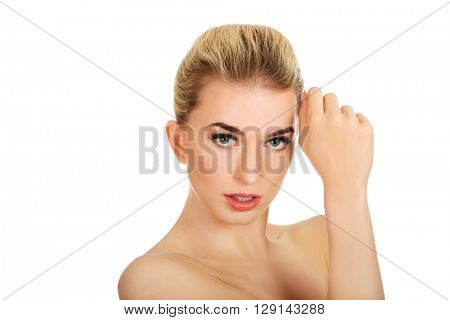 Young topless woman touching her face.