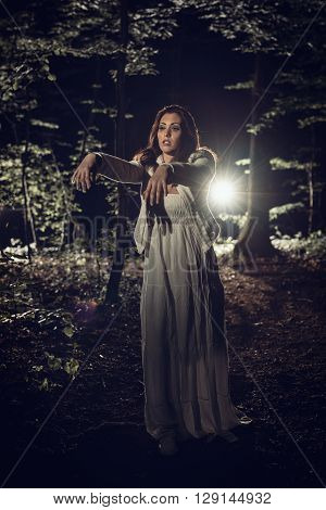 Young woman walking through the forest at night in white dress with outstretched arms in front of body.