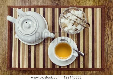 Top view of a cup of green tea teapot and sugar bowl on a wooden background
