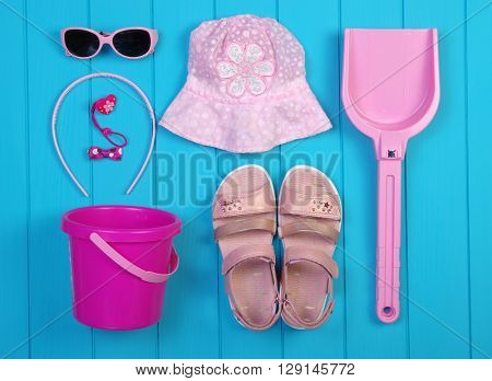 Summer accessories of girl on  blue wooden background