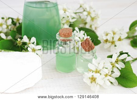 Natural herbal skincare, botanical cosmetic products. Facial tonic, essential oil, perfume in bottles, fresh flowers