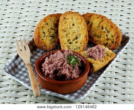 Delicious Homemade Meat Pate with Crispy Herbs Bread in Checkered Tray closeup on Wicker background