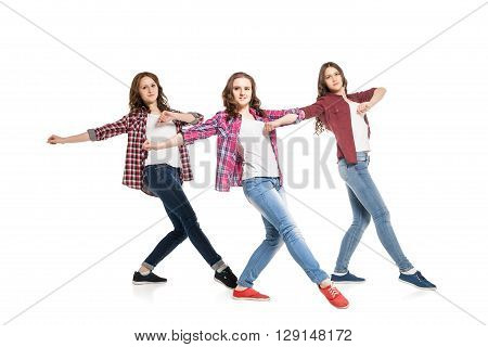 three young beautiful happiness women dancing over white background