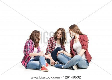 three young beautiful happiness women sitting over white background
