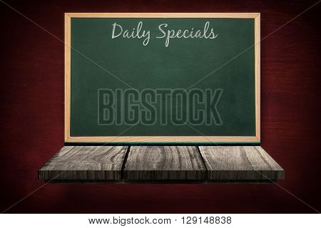 Daily specials message against blackboard on a wooden shelf