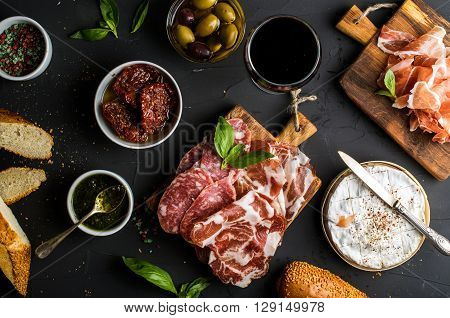 Wine snack set. Glass of red, meat selection, mediterranean olives, sun-dried tomatoes, baguette slices, camembert cheese and spices on black background, top view