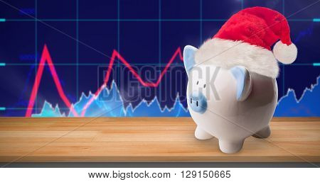 Image of a money-box with Christmas hat against stocks and shares