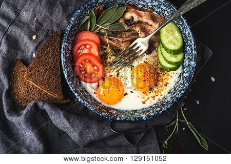 Breakfast set. Pan of fried eggs with bacon, fresh tomato, cucumber, sage and bread on dark serving board over black background, top view