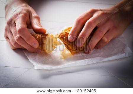 Hands tear off a piece of French pastry Croissant on white baking paper.