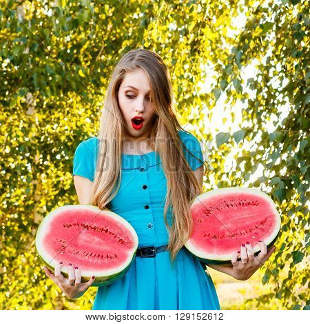 Beautiful blonde girl in a blue dress with long hair holding two halves of a sliced watermelon