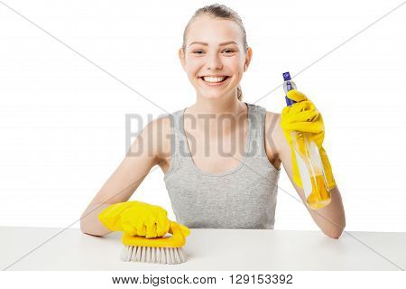 Young woman with scrub brush and cleansing spray for window, close-up, housewife, isolated on white