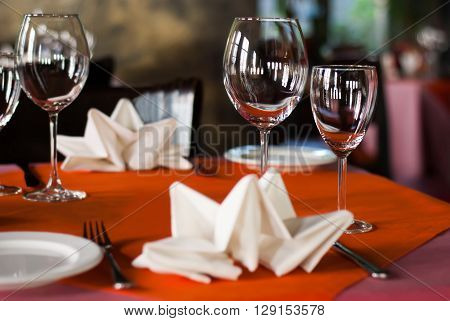 Romantic dinner interior, hotel service concept. Served table in a banquet hall. White plate knife fork and wine glasses on red napkin. Soft focus
