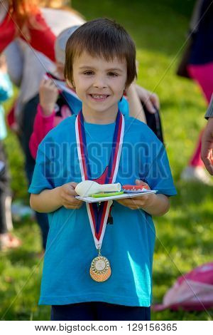 Proud Preschool Boy, Holding Prizes And Medals
