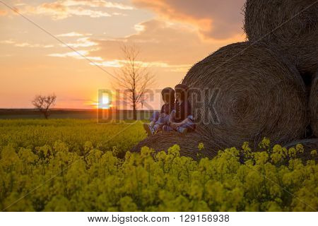 Two Children, Boy Brothers In A Oilseed Rape Field, Sitting On A Bale Of Haystacks, Watching Sunset