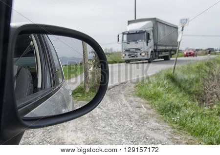Dirt road seen from the rearview mirror