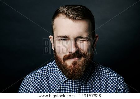 Winking red bearded handsome stylish man in blue checkered shirt, close up studio portrait on dark background