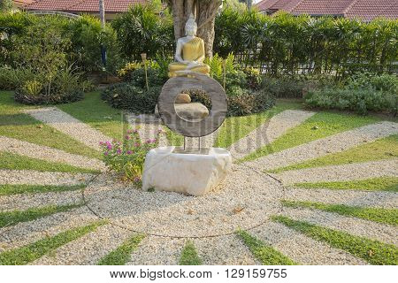 meditating silver buddha statue with golden robe in garden