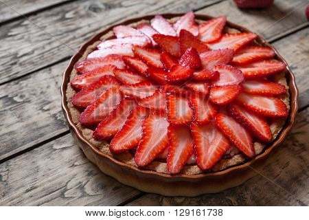 Traditional strawberry tart on vintage wooden background. Delicious summer pastry dessert food.