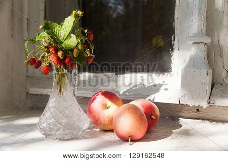 Still life with red apples and strawberries in a vase. old window sill, village house background. Summer, sunny day