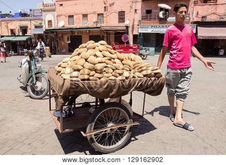 MARRAKECH MOROCCO - APR 29 2016: Street vendor selling Moroccan bread from a cart in the Medina of Marrakech