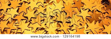 Frame full of gold stars,  wide format. Shallow depth of field.