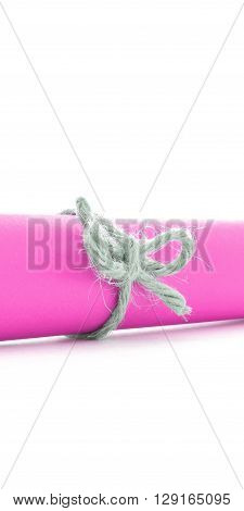 Handmade natural cord node tied on pink paper tube isolated