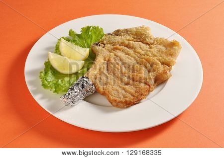 Plate with a portion of breaded cutlet Milanese