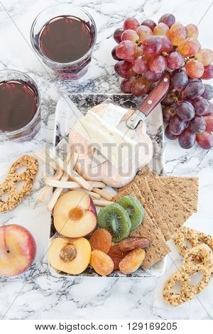 Selection of soft cheeses with crackers and fresh fruits